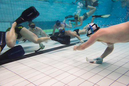 Underwater hockey player going for goal with defenders trying to stop him